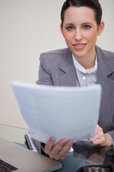 Geschäftsfrau, die schreibarbeit überreicht