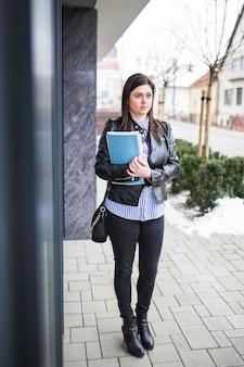 Geschäftsfrau, die schwarze jacke mit den büchern stehen auf bürgersteig trägt