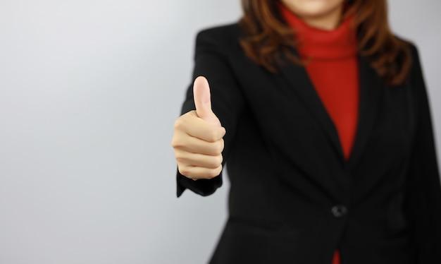 Geschäftsfrau, die schwarze und rote geschäftsanzuguniform mit selbstbewusstsein trägt, während daumen oben zeigt