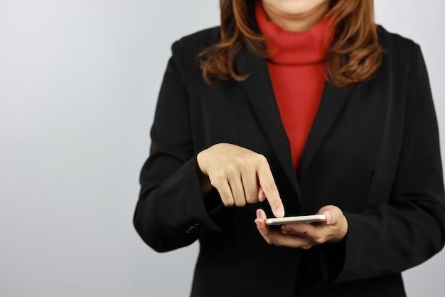 Geschäftsfrau, die schwarze und rote geschäftsanzuguniform trägt, die handy mit selbstbewusstsein hält und berührt