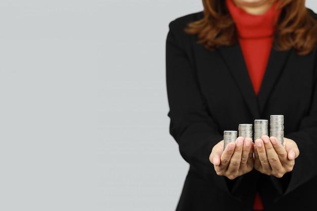 Geschäftsfrau, die schwarze und rote geschäftsanzuguniform trägt, die stapelmünzen mit zuversichtlich hält (geschäftswachstumswerbekonzept)