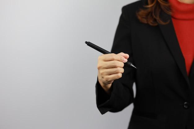 Geschäftsfrau, die schwarzen und roten geschäftsanzuguniform trägt, der stift hält und etwas mit selbstbewusstsein zeichnet (geschäftswachstumswerbekonzept)