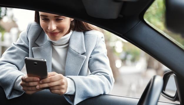Geschäftsfrau, die sich auf autofenster und sms am telefon stützt und glücklich lächelt.