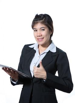 Geschäftsfrau, die sich daumen zeigt und eine tablette hält