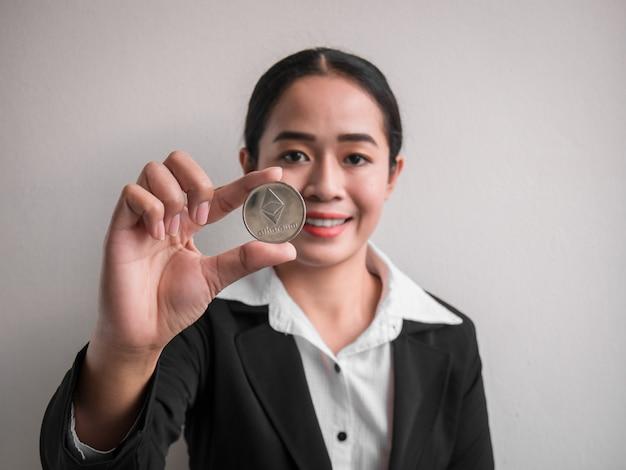 Geschäftsfrau, die silberne äthereummünze zeigt.