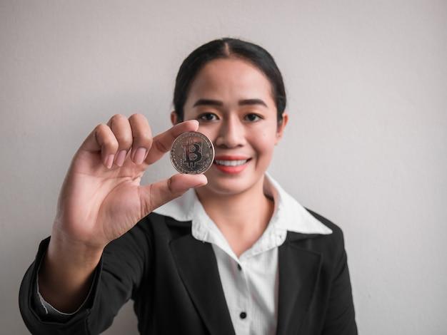 Geschäftsfrau, die silbernes bitcoin zeigt.
