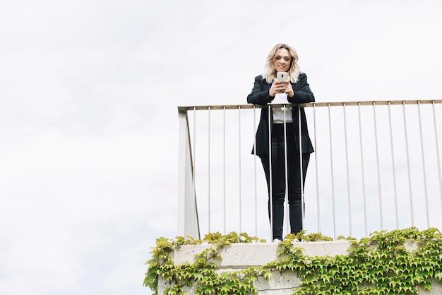 Geschäftsfrau, die smartphone auf balkon verwendet