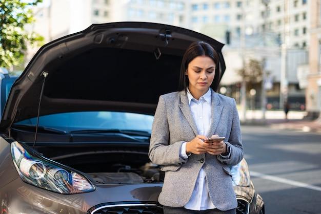 Geschäftsfrau, die smartphone benutzt, um hilfe für ihr kaputtes auto zu bekommen