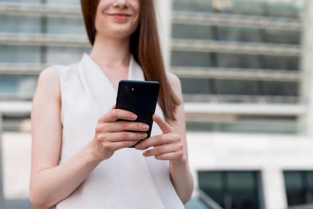 Geschäftsfrau, die smartphone in der straße verwendet