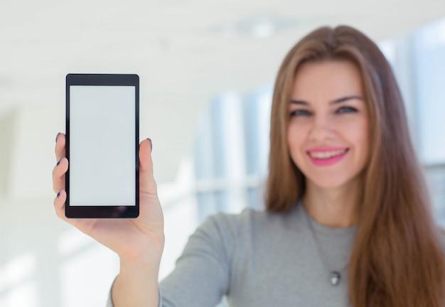 Geschäftsfrau, die smartphoneanzeige zur kamera demonstriert