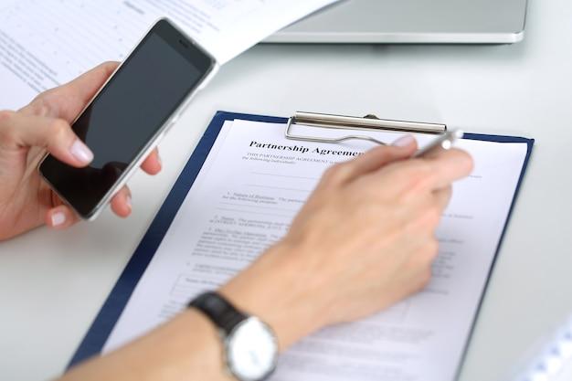Geschäftsfrau, die smartphonebildschirm betrachtet, bereit, partnerschaftsvereinbarung geschäfts- und partnerschaftskonzept zu unterzeichnen