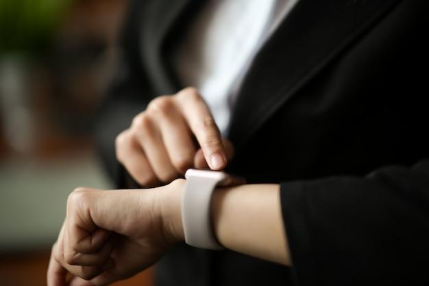 Geschäftsfrau, die smartwatch betrachtet und zeigt