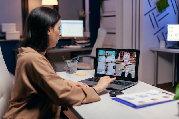 Geschäftsfrau, die spät in der nacht eine videokonferenz führt und über die projektfrist diskutiert. freiberufler, der während einer videokonferenz mit kollegen nachts im büro an finanzen arbeitet.