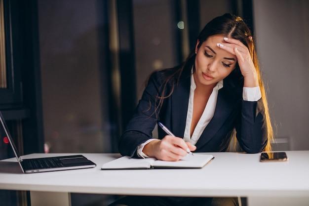 Geschäftsfrau, die spät nachts am computer im büro arbeitet