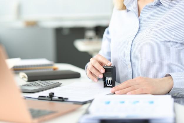 Geschäftsfrau, die stempel auf dokument im amt setzt
