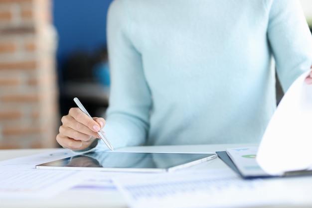 Geschäftsfrau, die stift in den händen über tablettennahaufnahme hält. konzept der jährlichen rechnungslegungsberichte