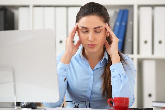 Geschäftsfrau, die stress am arbeitsplatz erlebt und ihre hand hinter dem kopf hält