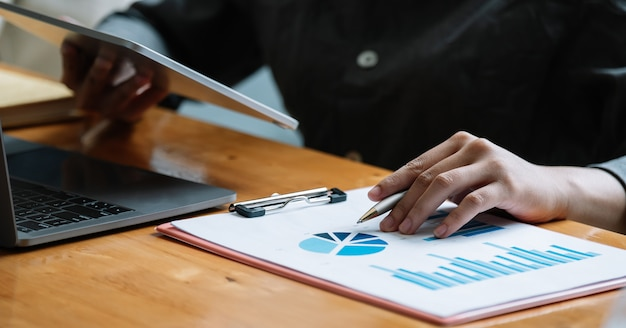 Geschäftsfrau, die tablet-computer für analyse-finanzbericht verwendet