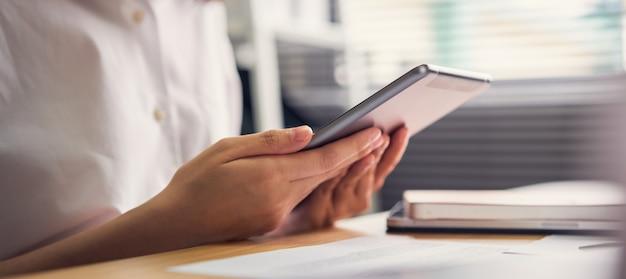 Geschäftsfrau, die tablette hält und verwendet, um online auf dem tisch im büro zu arbeiten.