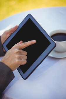 Geschäftsfrau, die tablette mit kaffee verwendet