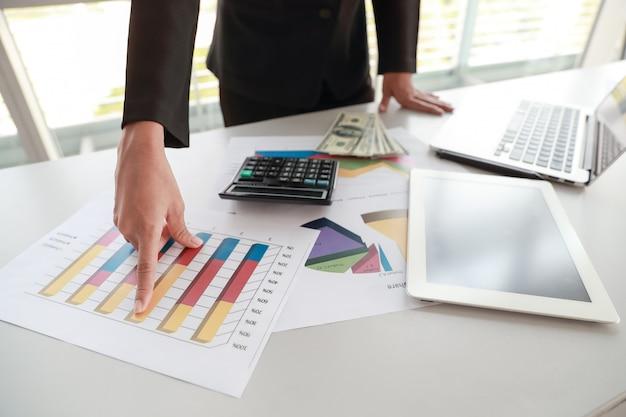 Geschäftsfrau, die tablette und computer beim arbeiten an firmenzusammenfassungsbericht mit diagramm verwendet
