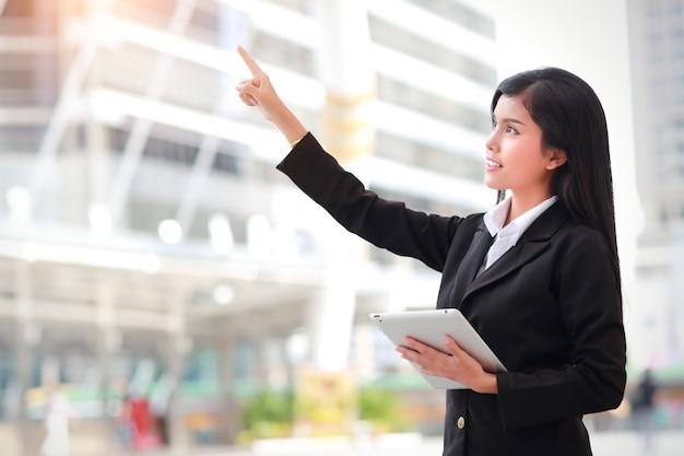 Geschäftsfrau, die tablette verwendet und finger zeigt