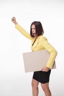 Geschäftsfrau, die tafel oder fahne mit kopienraum auf weißer wand zeigt
