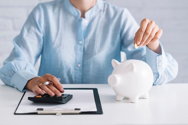 Geschäftsfrau, die taschenrechner beim einstecken der münze in piggybank am arbeitsplatz verwendet