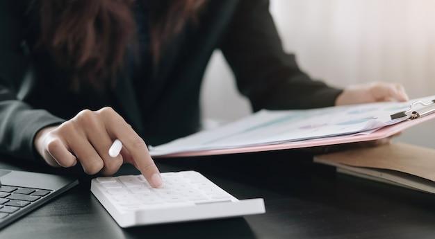 Geschäftsfrau, die taschenrechner verwendet, um mathematische finanzen auf holzschreibtisch im büro zu erledigen?