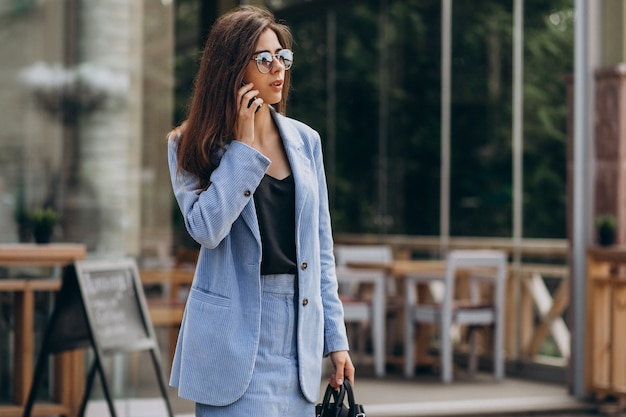 Geschäftsfrau, die telefon außerhalb der straße benutzt