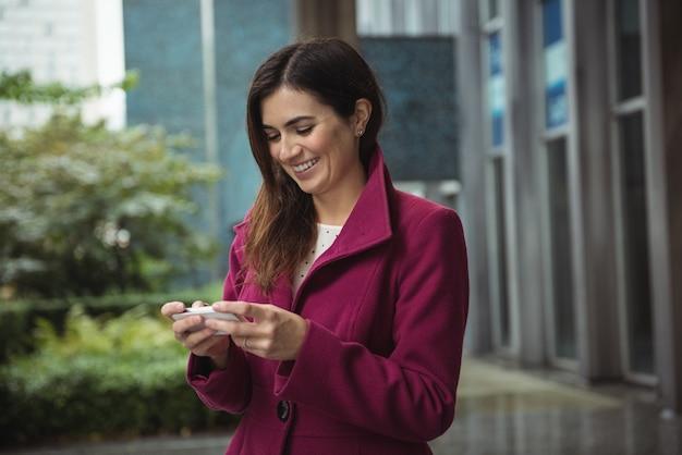 Geschäftsfrau, die telefon außerhalb des büros benutzt