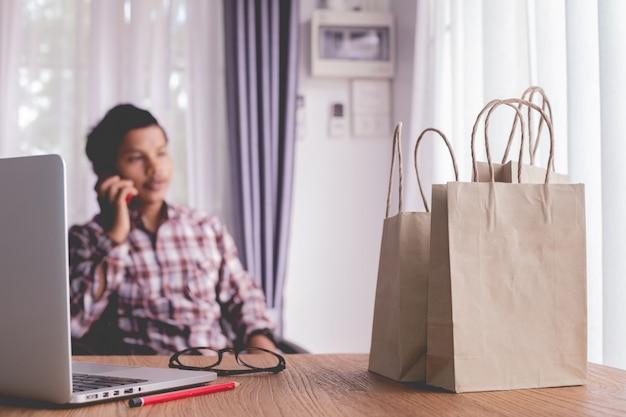 Geschäftsfrau, die telefon für das einkaufen online verwendet.
