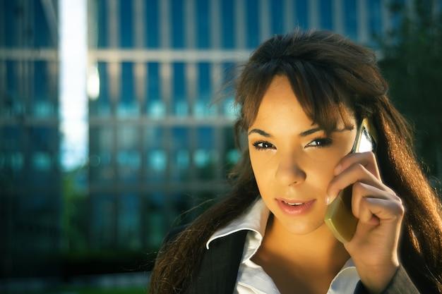 Geschäftsfrau, die telefonisch bei sonnenuntergang spricht