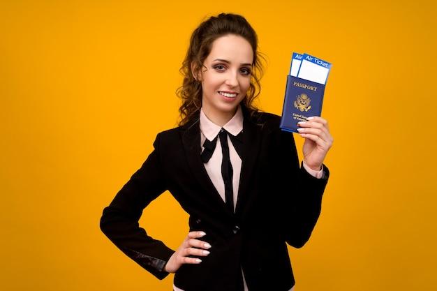 Geschäftsfrau, die tickets und pass auf gelbem studio-hintergrund hält