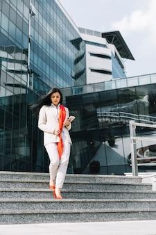 Geschäftsfrau, die treppenhaus vor gebäude hinunterbewegt