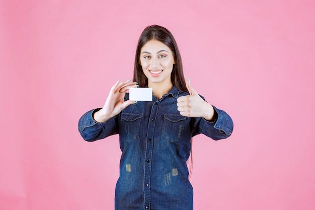 Geschäftsfrau, die visitenkarte hält und genusshandzeichen zeigt