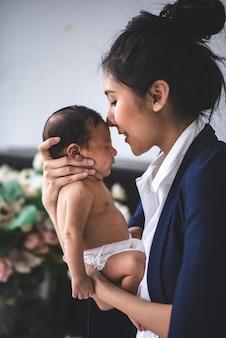 Geschäftsfrau, die vom haus, baby halten arbeitet