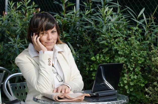 Geschäftsfrau, die vor einem laptop sitzt, während sie am telefon spricht