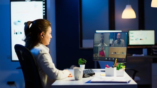 Geschäftsfrau, die während der videokonferenz mit dem team um mitternacht unter verwendung des pcs im start-up-geschäftsbüro spricht. unternehmensmeeting mit drahtlosem technologienetzwerk, das spät in der nacht vor der webcam diskutiert