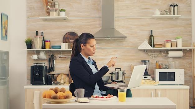 Geschäftsfrau, die während des frühstücks auf videoanruf winkt. junge freiberuflerin in der küche, die eine gesunde mahlzeit zu sich nimmt, während sie mit ihren kollegen aus dem büro in einem videoanruf spricht und moderne technologie verwendet