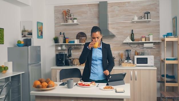 Geschäftsfrau, die während des frühstücks im büro hetzt. junge freiberuflerin, die rund um die uhr arbeitet, um ihre ziele zu erreichen, stressige lebensweise, eile, zu spät zur arbeit, immer auf der flucht