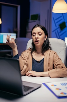 Geschäftsfrau, die während des online-anrufs ohrhörer verwendet und überstunden macht. frau, die während einer videokonferenz mit kollegen nachts im büro an finanzen arbeitet.