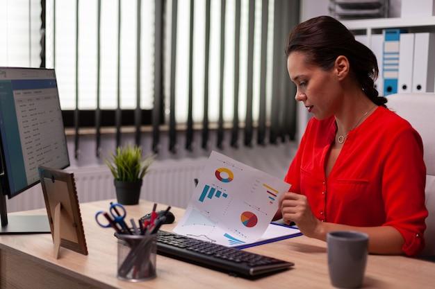 Geschäftsfrau, die während des professionellen geschäftsanrufs am schreibtisch sitzt und rot trägt. beschäftigter freiberufler, der mit dem smartphone vom büro aus arbeitet, um mit kunden zu sprechen, die am schreibtisch sitzen und das dokument betrachten.