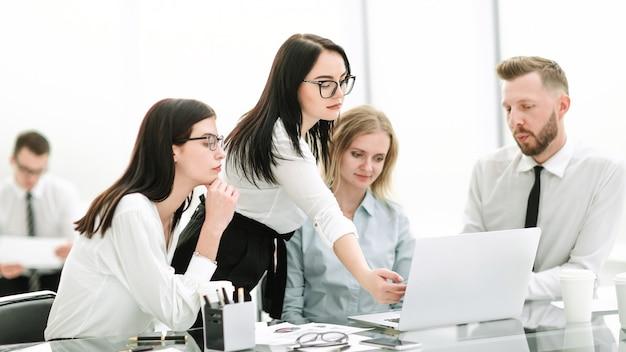 Geschäftsfrau, die während eines treffens mit dem geschäftsteam auf den laptopbildschirm zeigt