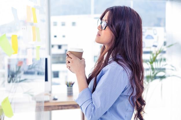 Geschäftsfrau, die wegwerfschale hält und wand mit anmerkungen im büro betrachtet