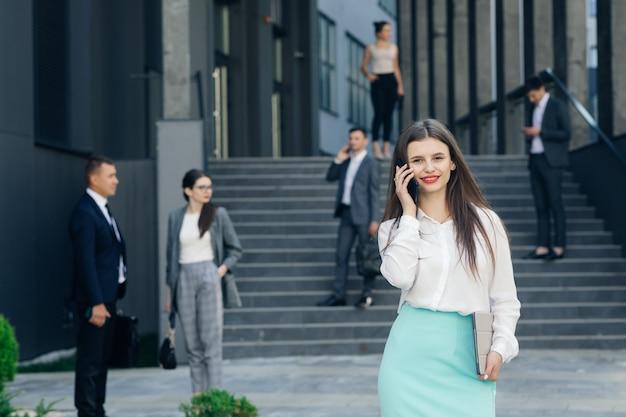 Geschäftsfrau, die weißes hemd unter verwendung des modernen smartphones trägt. professioneller weiblicher arbeitgeber, der textnachricht auf handy außerhalb schreibt.