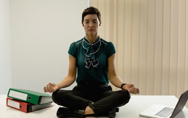 Geschäftsfrau, die yoga im büro praktiziert