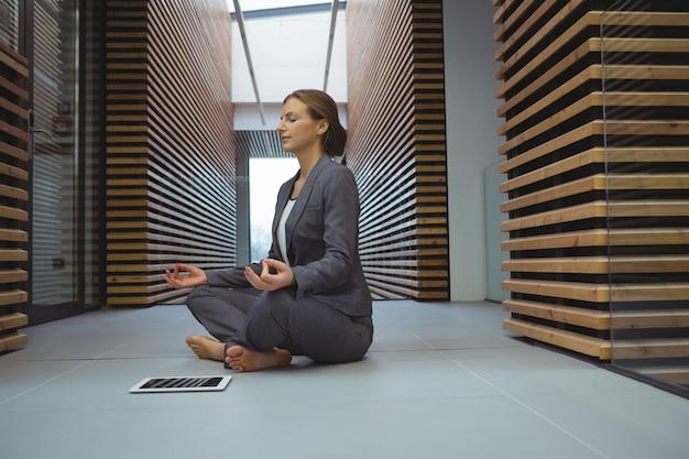 Geschäftsfrau, die yoga im korridor durchführt