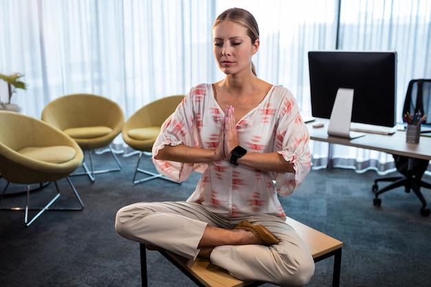 Geschäftsfrau, die yoga mit den händen gebunden tut