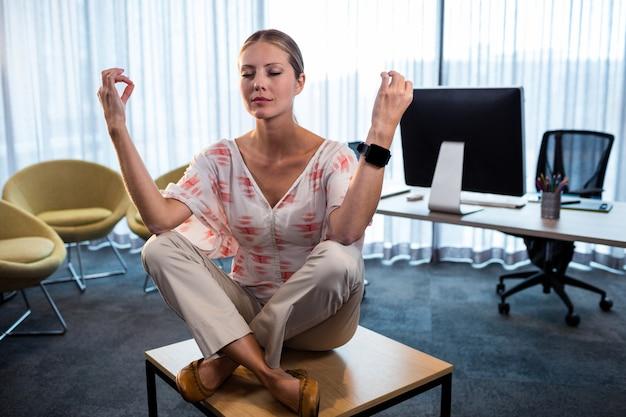 Geschäftsfrau, die yoga mit den händen in der luft tut